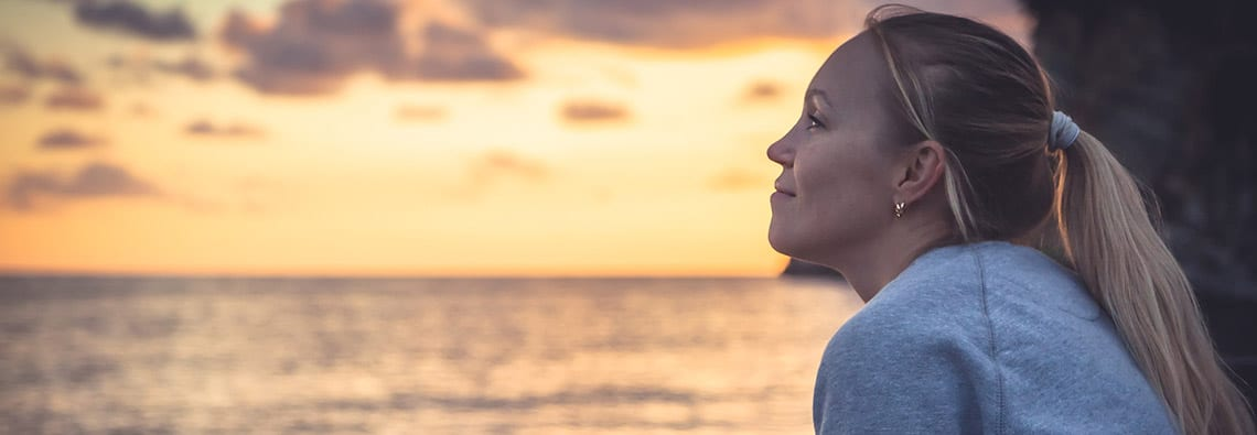 woman-watching-sunset-by-bench-for-mental-health-treatment