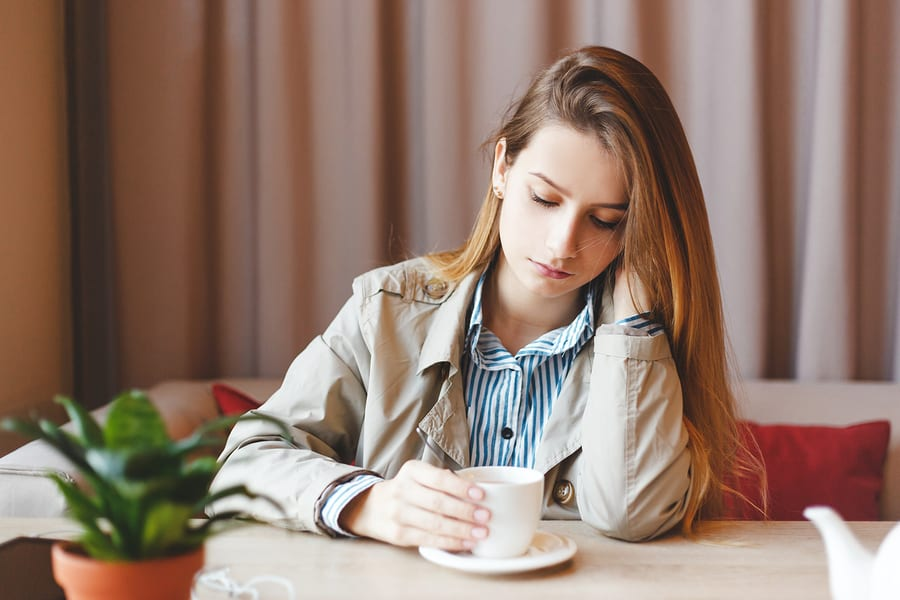 Woman looking at cup of coffee
